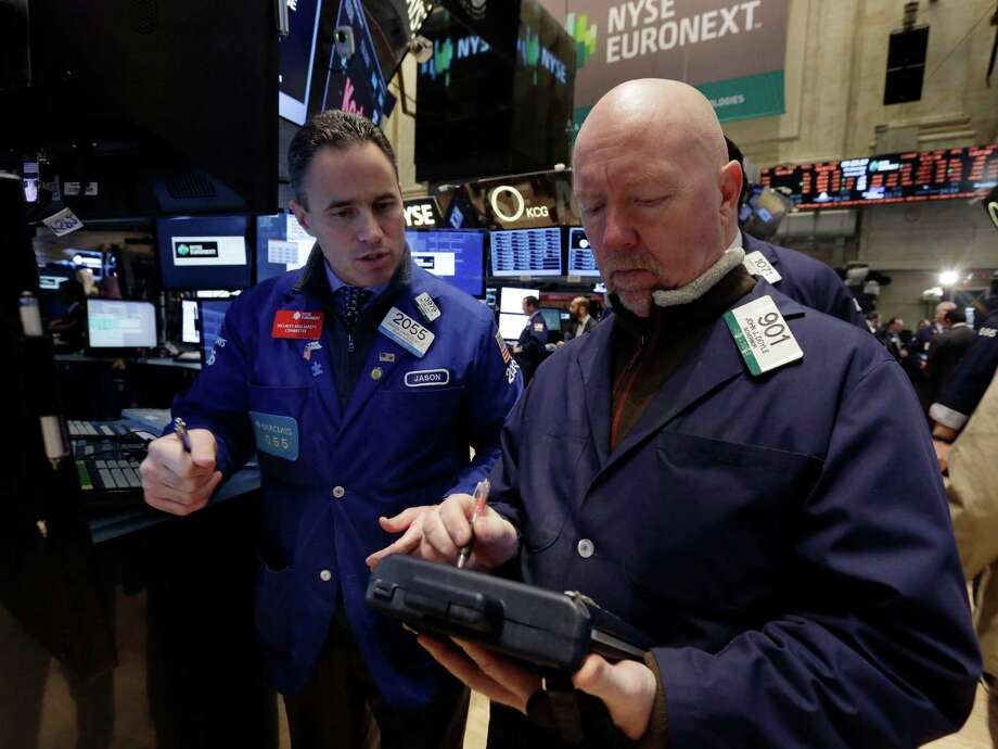 FILE - In this Wednesday, Jan. 8, 2014, file photo, specialist Jason Hardzewicz, left, and trader John Doyle work on the floor of the New York Stock Exchange. Stock indexes are slightly higher in early trading Friday, Jan. 10, 2014. (AP Photo/Richard Drew, File) ORG XMIT: NY120 Photo: Richard Drew / AP