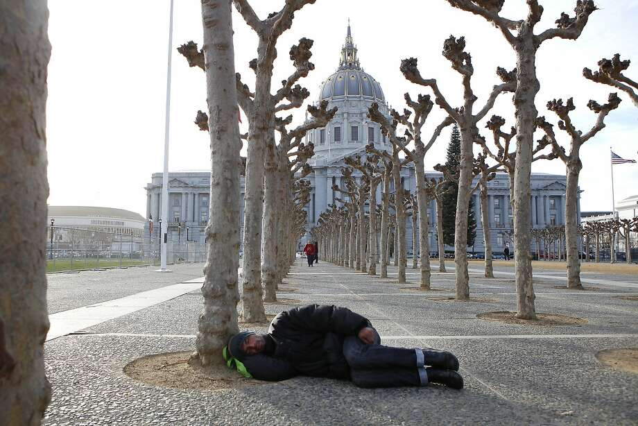 A person sleeps on the ground at Civic Center Plaza across from San Francisco's City Hall in January. Photo: Michael Short, The Chronicle
