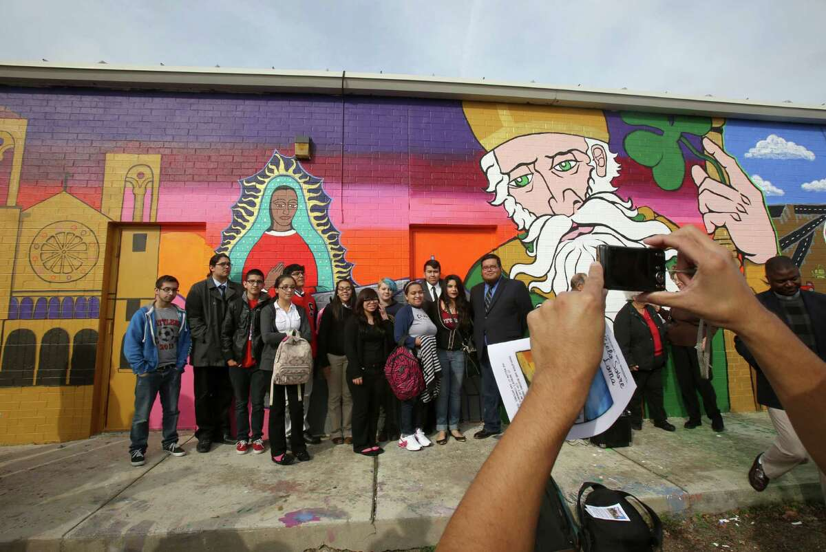 Students from City Center Health Careers Charter School pose for a photo in front of the new mural at St. Patrick's Community Center as part of the mural blessing on Friday Jan. 10. 2014. San Anto Cultural Arts dedicated its 45th community mural
