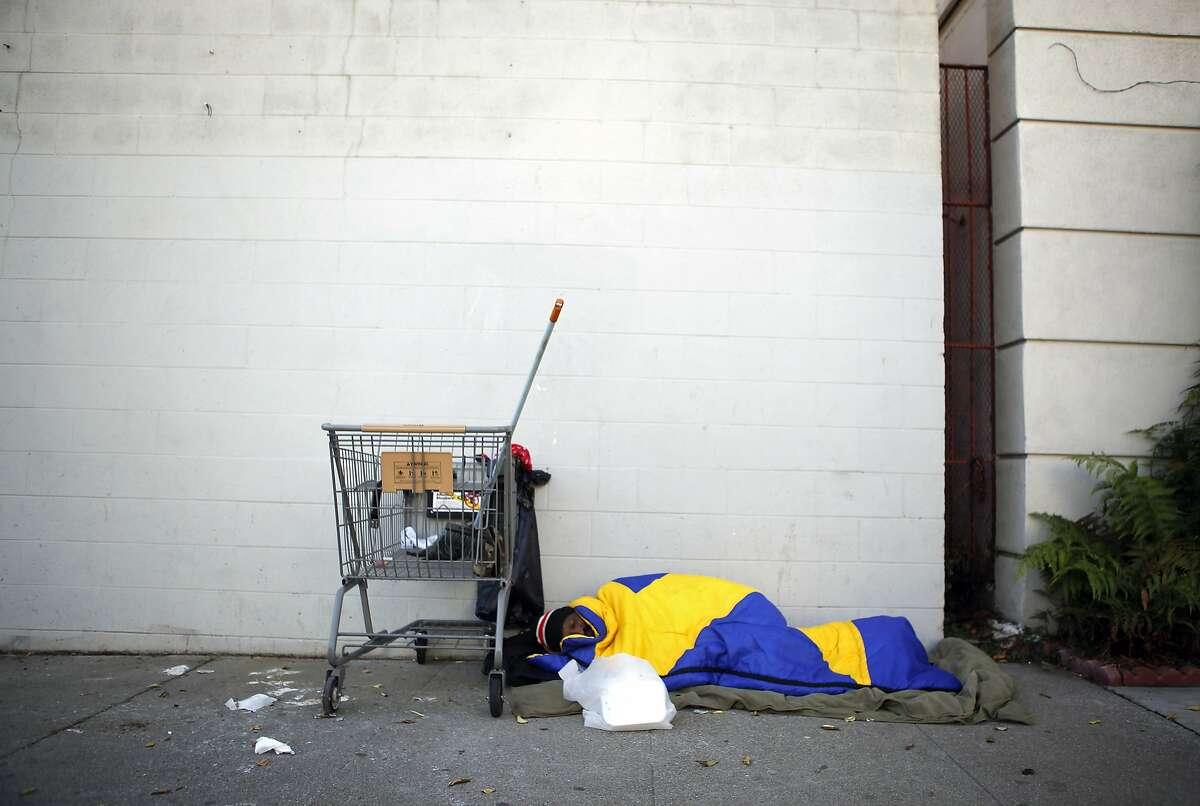 A homeless man sleeps on the sidewalk on Octavia St. in San Francisco, CA, Thursday, January 9, 2014.