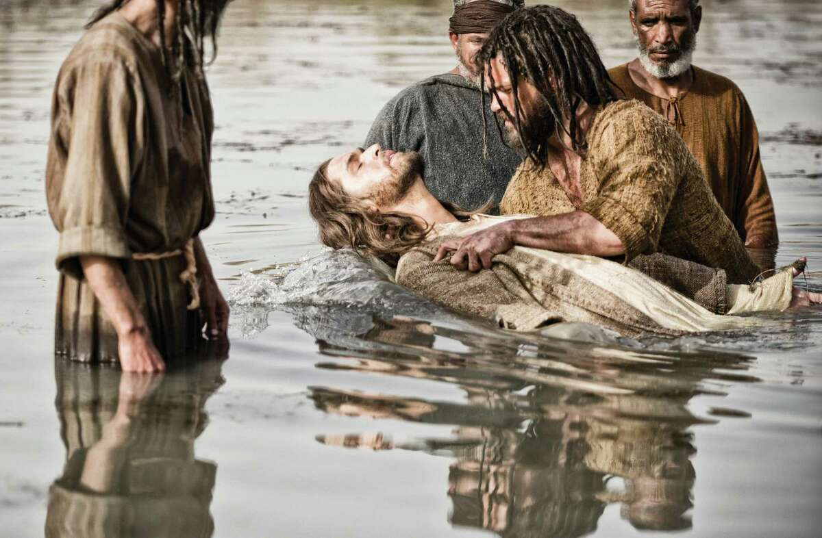 Diogo Morcaldo (center) portrays Jesus, being baptized by John, played by Daniel Percival, in a scene from