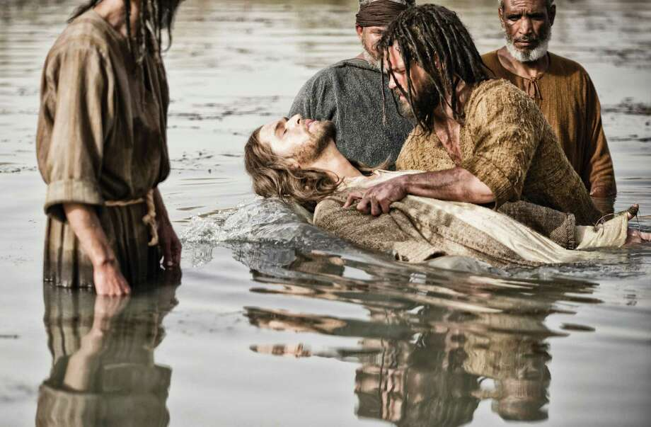 "Diogo Morcaldo (center) portrays Jesus, being baptized by John, played by Daniel Percival, in a scene from ""The Bible."" Photo: Joe Alblas / Associated Press / History"