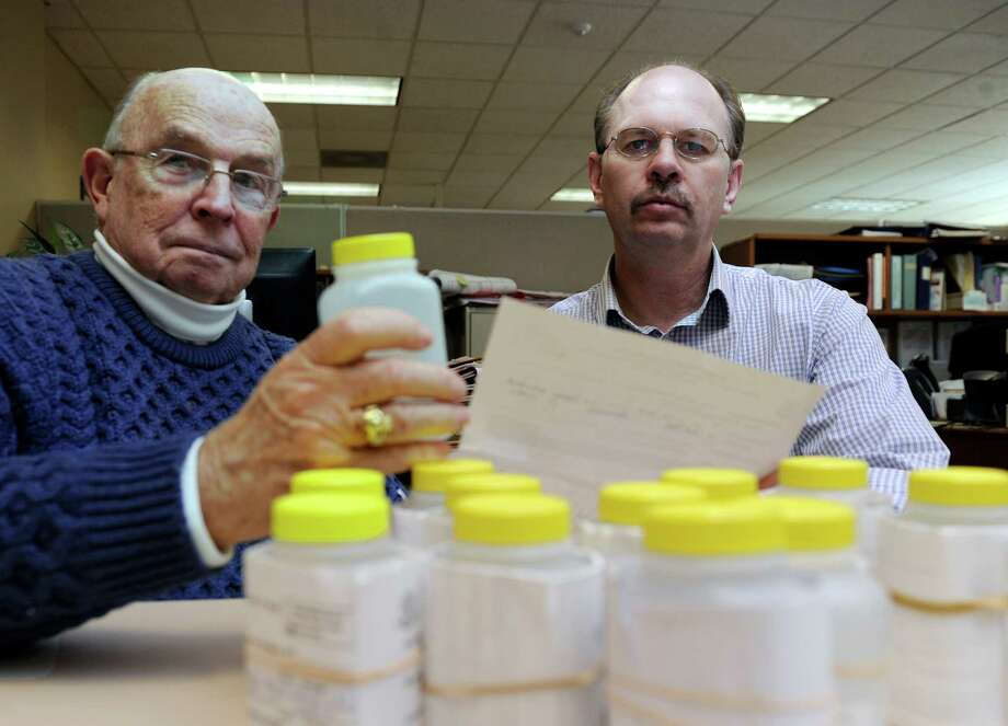 Dr. Raymond E. Sullivan, left, director of Health for Brookfield, Conn., and Paul Avery, town sanitarian, have collected water samples from private well owners in Brookfield, to be tested for arsenic and uranium. They are photographed with some of the samples Wednesday, January 8, 2014. Photo: Carol Kaliff / The News-Times