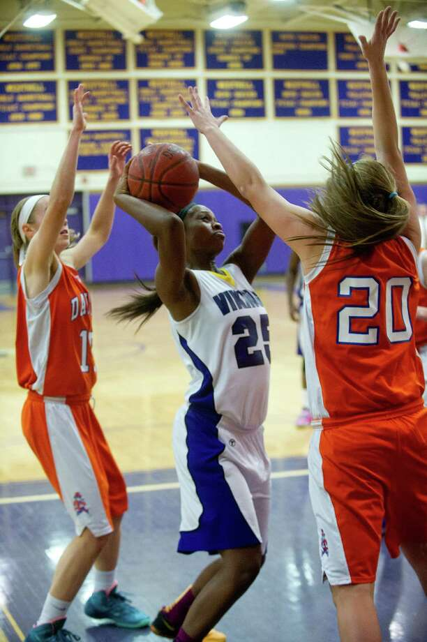 Westhill's Krystal Dixon takes a shot as she is guarded by Danbury's Rebecca Gartner, left, and Allie Smith, right, during Friday's girls basketball game at Westhill High School in Stamford, Conn., on January 10, 2014. Photo: Lindsay Perry / Stamford Advocate