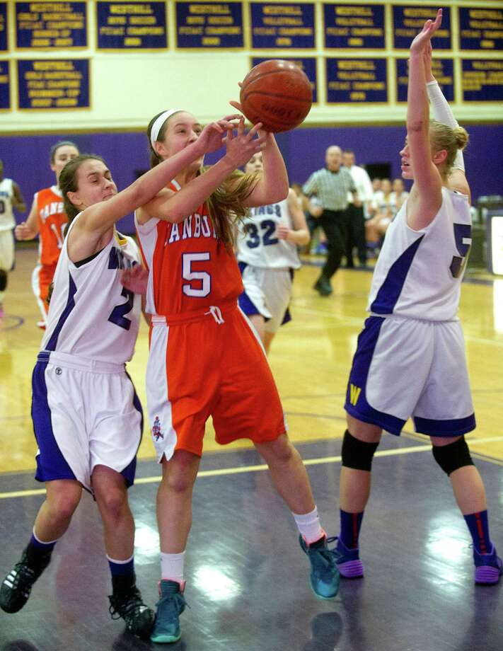 Danbury's Rachel Gartner tries to hold on to the ball as she is defended by Westhill's Edona Thaqi, left, and Steph Roones, right, during Friday's girls basketball game at Westhill High School in Stamford, Conn., on January 10, 2014. Photo: Lindsay Perry / Stamford Advocate