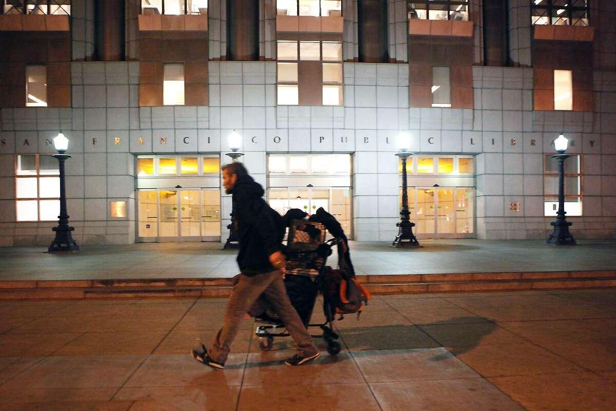 A man wheels a shopping cart past the Main Library at Civic Center Plaza in San Francisco, CA, Thursday, January 9, 2014.