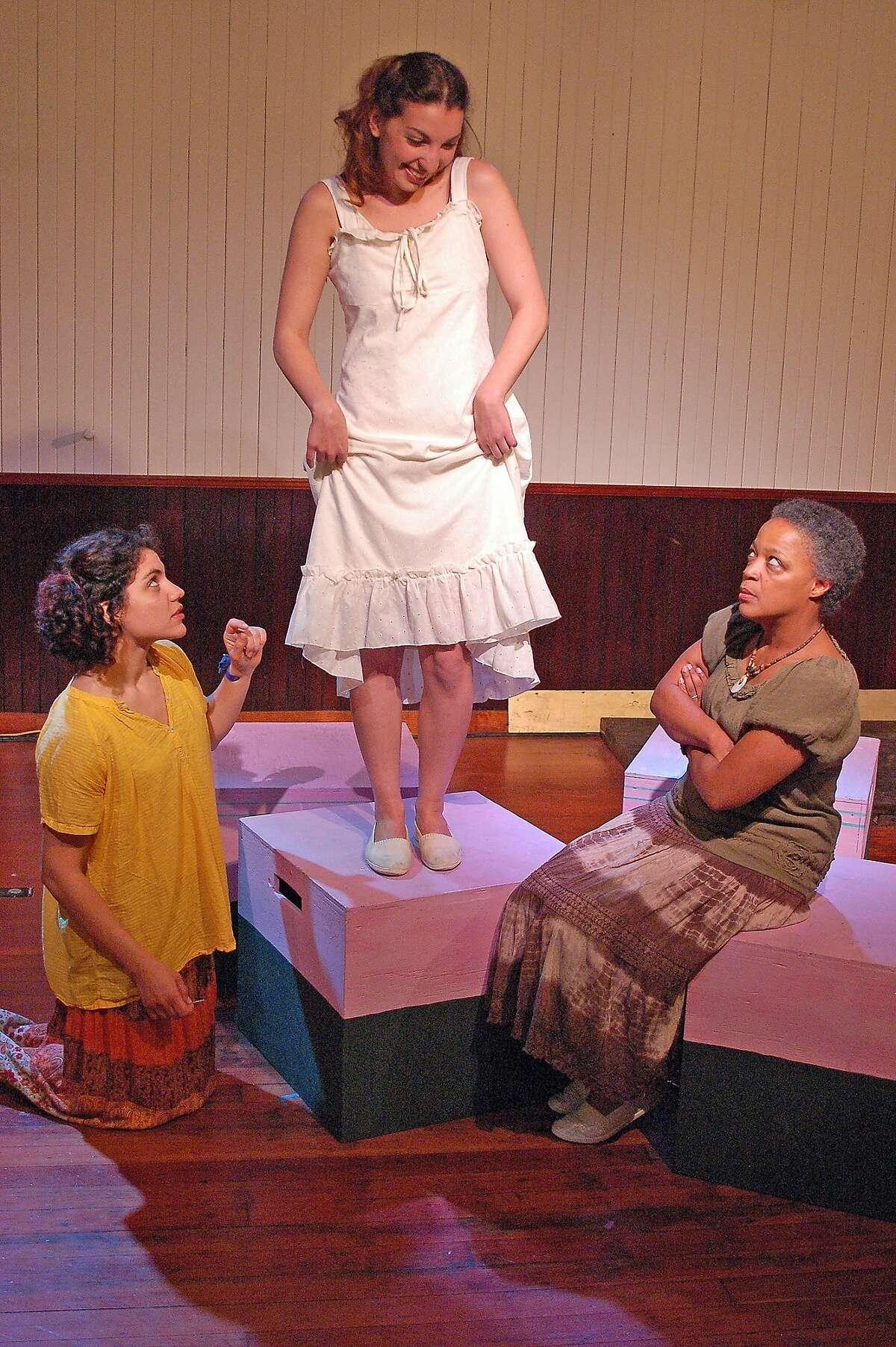 "Senhora Costa (Cathleen Riddley, right) and daughter Helena (Carla Pauli, left) help prepare Belmira's (Livia Demarchi, center) wedding dress in Alter Theater's ""The River Bride"""