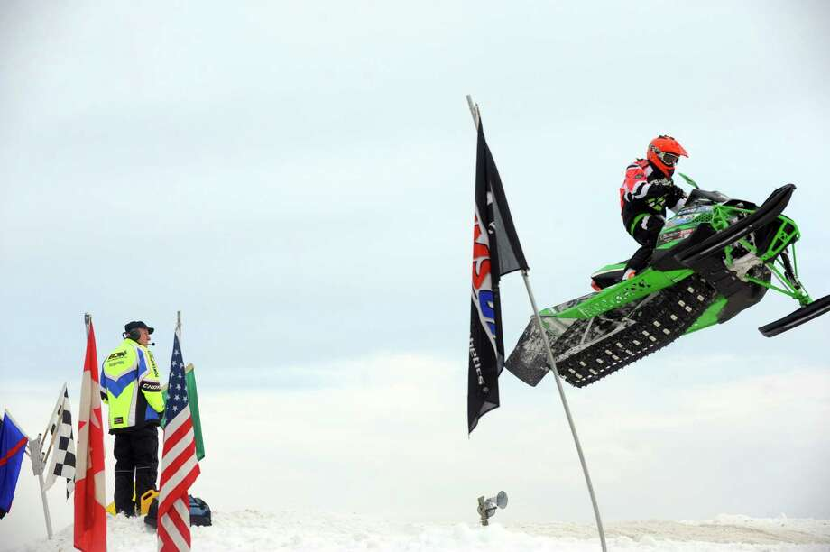 Finish line judge Larry Wierzba, left, watches as a racer Michael Newman of Stamford, Conn. takes to the air during a practice session during part of the East Coast Snocross Series at the Fonda Speedway on Friday afternoon, Jan. 10, 2014, in Fonda, N.Y. The event takes place Saturday and Sunday gates open at 10:30 A.M. each day, with pro racing getting under way at 12:30 P.M. Admission is $12 per day for adults, $10 for children ages 8-12, age 7 and under will be admitted free with a paying adult. Pit passes can be purchased for an extra $10. (Michael P. Farrell/Times Union) Photo: Michael P. Farrell / 00025326A