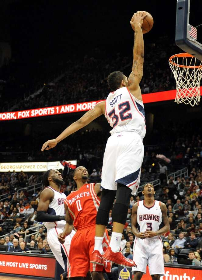 Hawks forward Mike Scott (32) dunks over Aaron Brooks. Photo: Dave Tulis, Associated Press