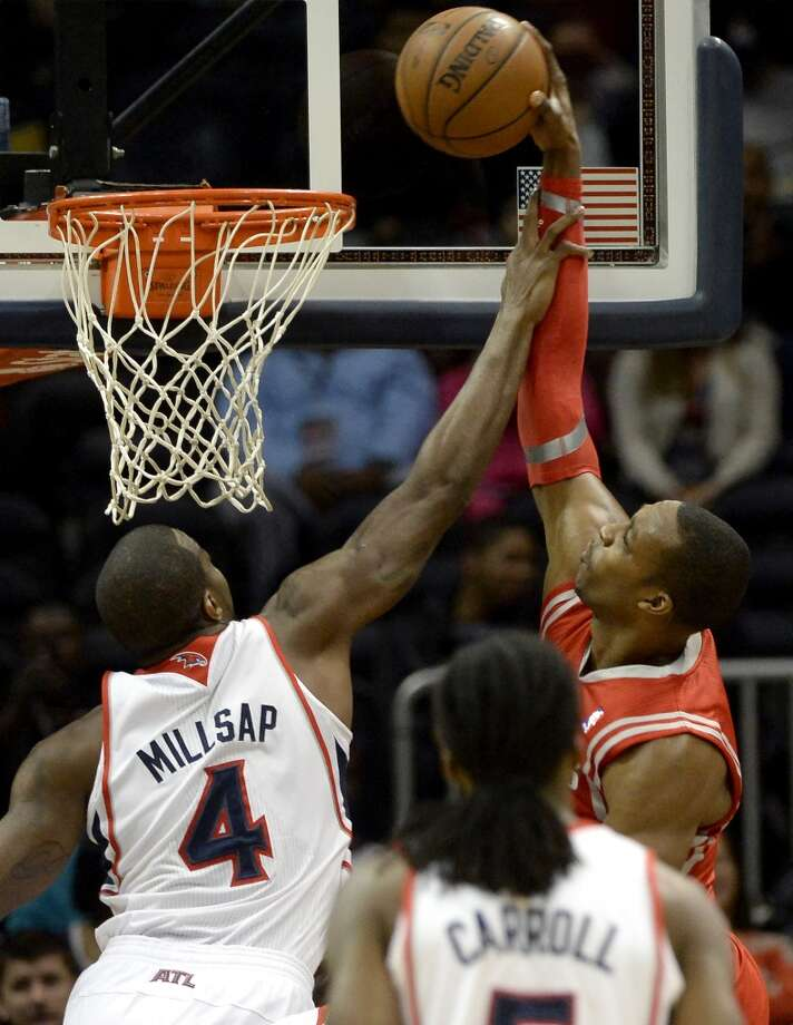 Rockets forward Dwight Howard, right, dunks over Paul Millsap. Photo: Dave Tulis, Associated Press
