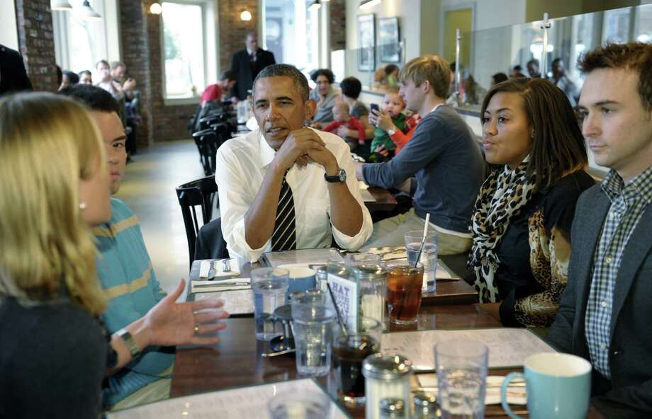 President Barack Obama listens as he has lunch with five young people at The Coupe restaurant in the Columbia Heights section of Washington. Photo: Susan Walsh / Associated Press / AP