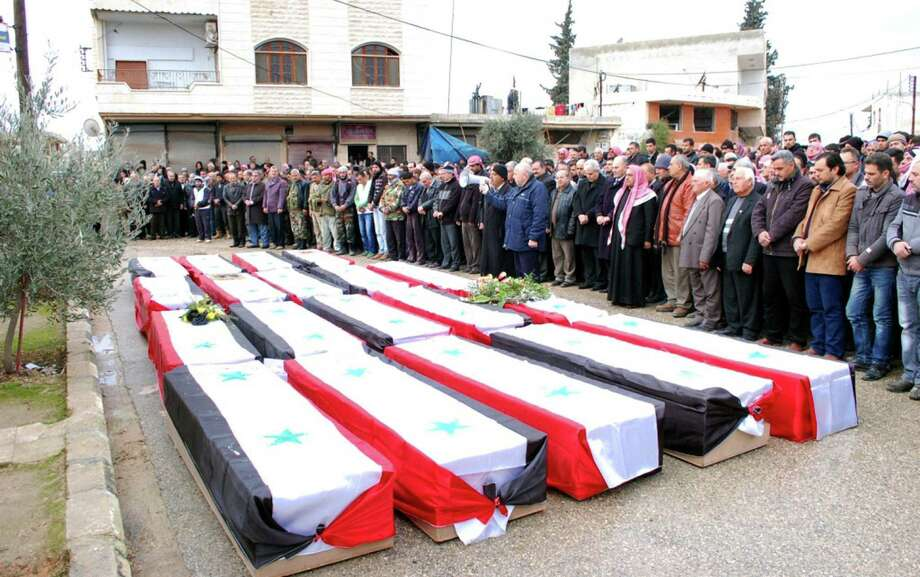 People pay their respects in a photo released by the official Syrian Arab News Agency during a funeral for victims of a massive car bomb in the village of Kafat, in the central province of Hama. Photo: AFP / SANA / AFP