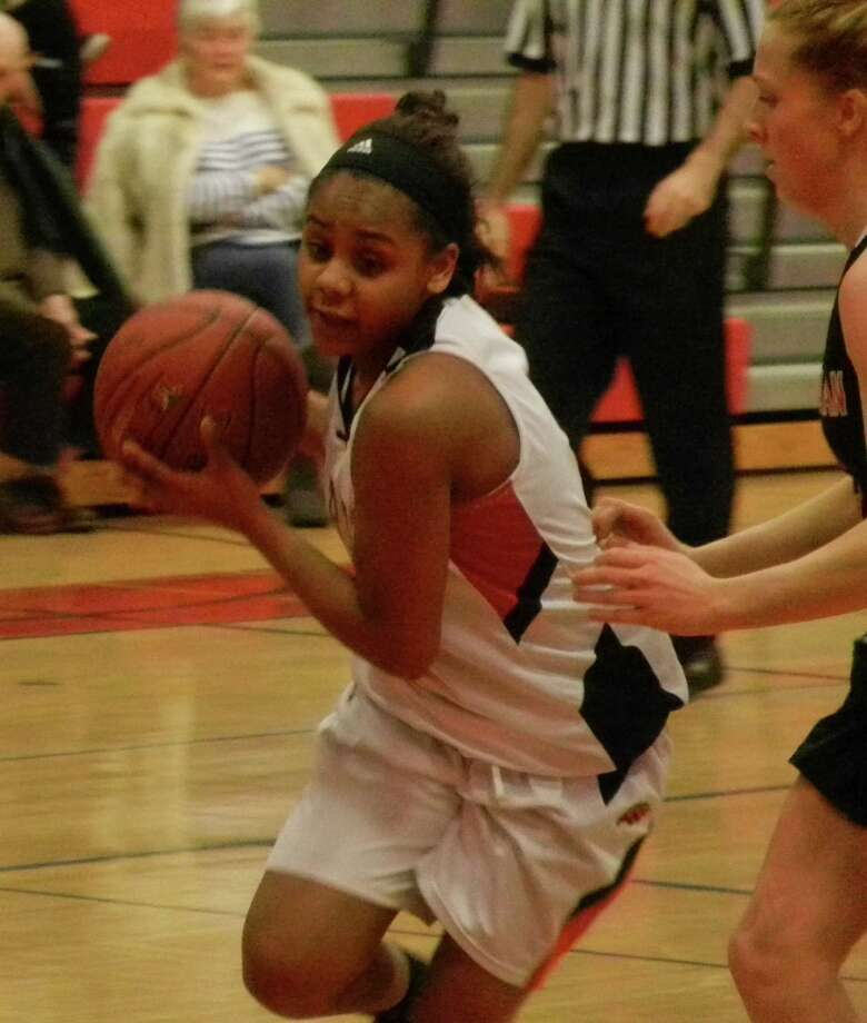 Daja Polk, of Fairfield Warde, cuts through the New Canaan defense on Friday, Jan. 10 in the Mustangs' 60-18 FCIAC girls basketball victory. Photo: Reid L. Walmark / Fairfield Citizen