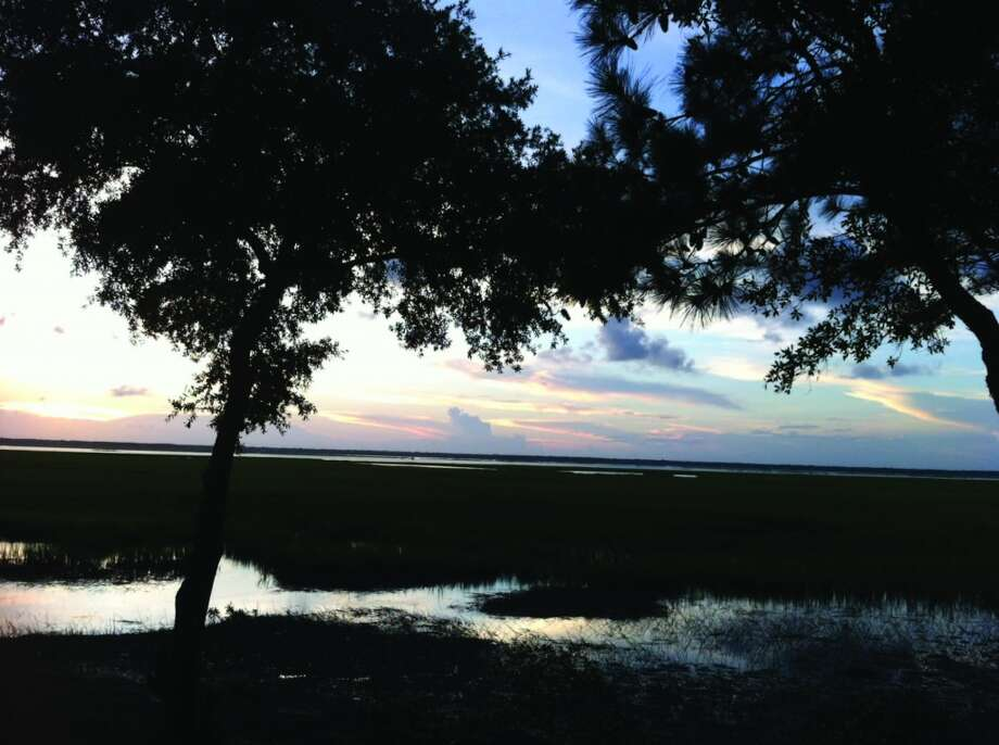 The sun sets over the marsh along one side of Dewees Island. Photo: Terry Scott Bertling, San Antonio Express-News