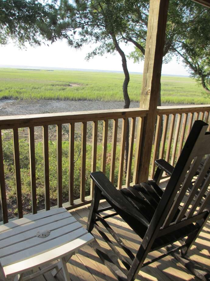 A few rockers line the front deck facing the marsh and the sunset at the Marsh House on Dewees Island. Photo: Terry Scott Bertling, San Antonio Express-News