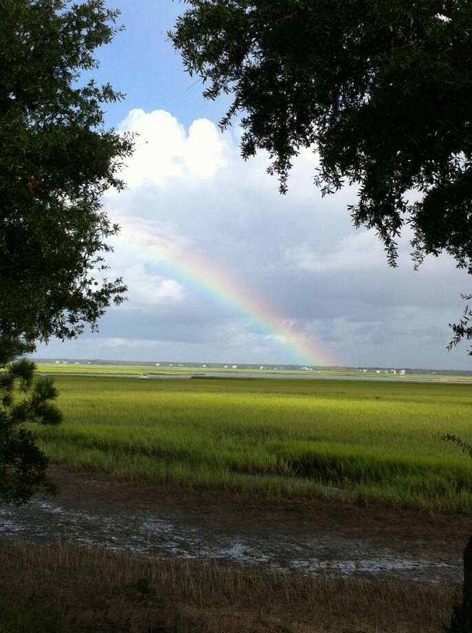 An afternoon shower leaves a rainbow over the marsh. Photo: Terry Scott Bertling, San Antonio Express-News
