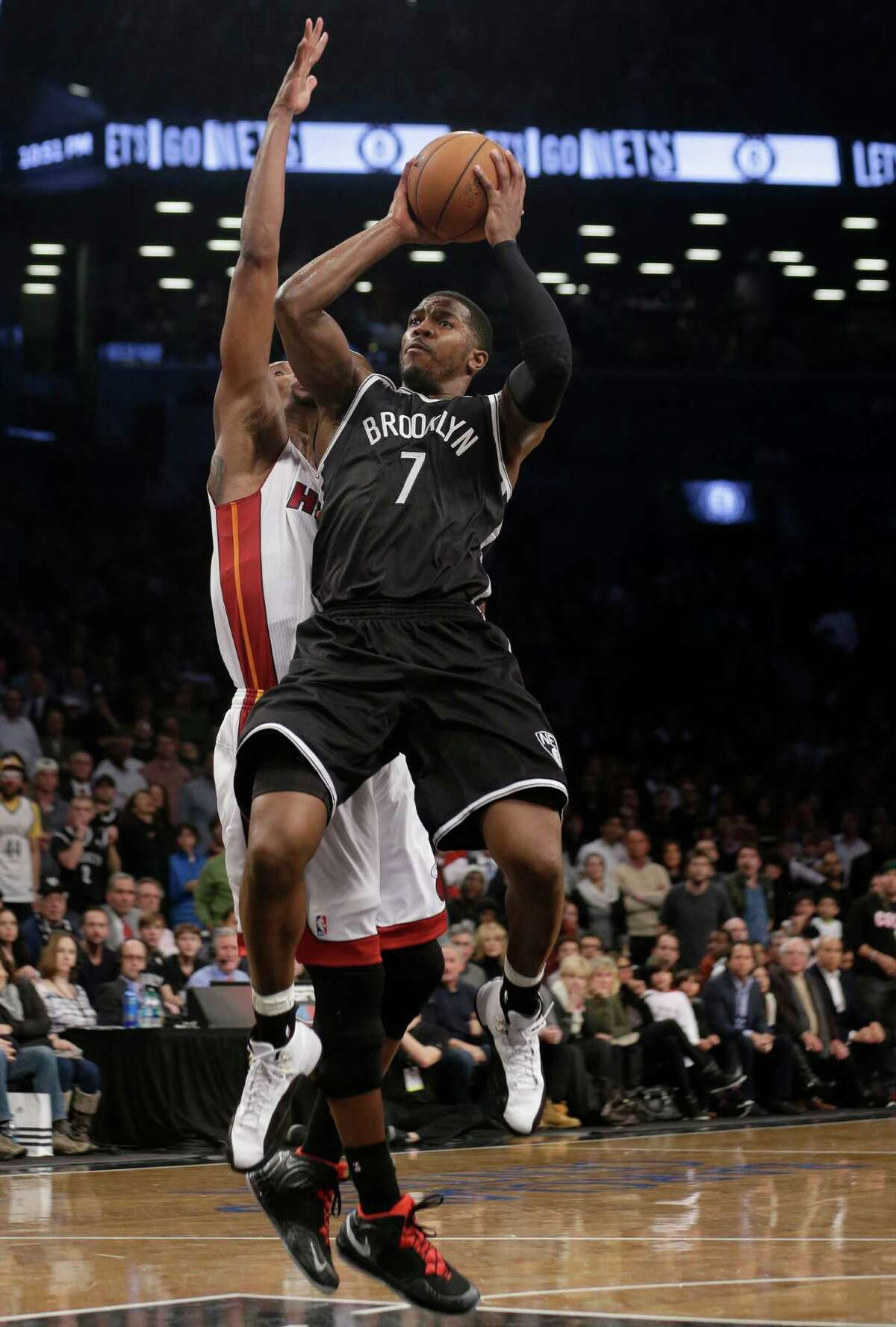 Brooklyn Nets' Joe Johnson (7) shoots over Miami Heat's Chris Bosh (1) during the first overtime period of an NBA basketball game on Friday, Jan. 10, 2014, in New York. The Nets won the game 104-95. (AP Photo/Frank Franklin II) ORG XMIT: NYFF114