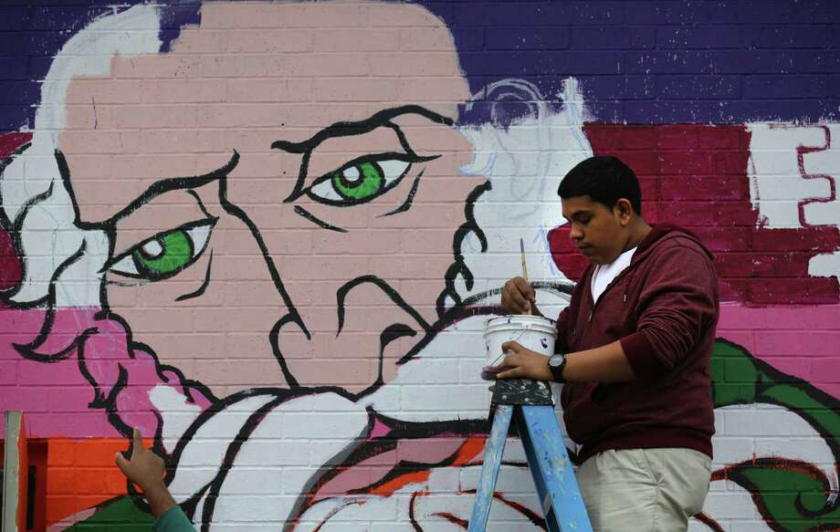 Abraham Ontiveros, a tenth grader at Center City Health Careers, paints on a mural at the school.  San Anto Cultural Arts has partnered with Center City Health Careers offering a mural class as an elective at the charter school.  Tenth grade students painting a mural on the side of the school. Friday, Dec. 13, 2013. Photo: BOB OWEN, San Antonio Express-News / © 2012 San Antonio Express-News