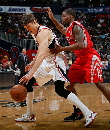 Atlanta's Kyle Korver keeps the ball from Houston's Aaron Brooks after cleaning up a missed shot in the Hawks' victory. Korver scored 20 points. Photo: Kevin C. Cox / Getty Images / 2014 Getty Images