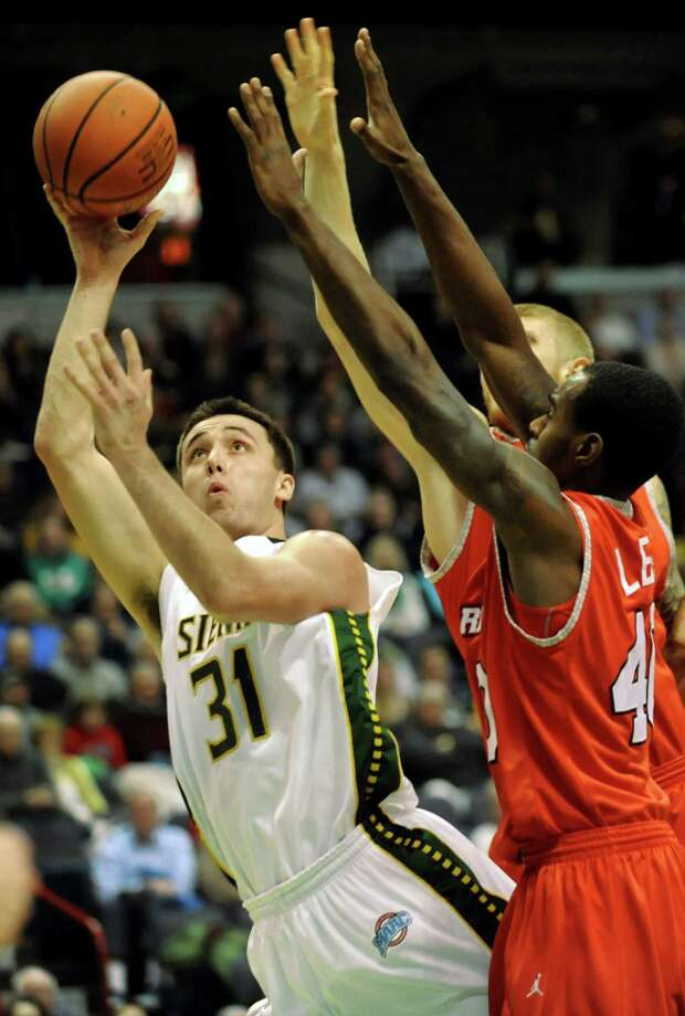 Siena's Brett Bisping, left, shoots for the hoop as Marist's Chavaughn Lewis defends during their basketball game on Friday, Jan. 10, 2014, at Times Union Center in Albany, N.Y. (Cindy Schultz / Times Union) Photo: Cindy Schultz / 00025111D