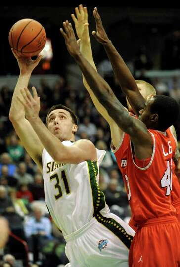 Siena's Brett Bisping, left, shoots for the hoop as Marist's Chavaughn Lewis defends during their ba