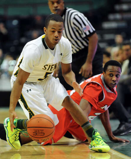 Siena's Evan Hymes, left, picks up a loose ball over Marist's Manny Thomas during their basketball g