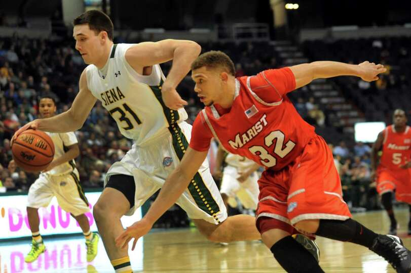 Siena's Brett Bisping, left, controls the ball as Marist's T.J. Curry defends during their basketbal