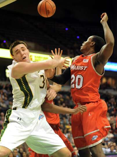 Siena's Brett Bisping, left, goes up against Marist's Jay Bowie for a rebound during their basketbal