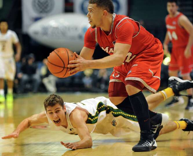 Siena's Rob Poole, left, gets tripped up as he defends against Marist's T.J. Curry during their bask