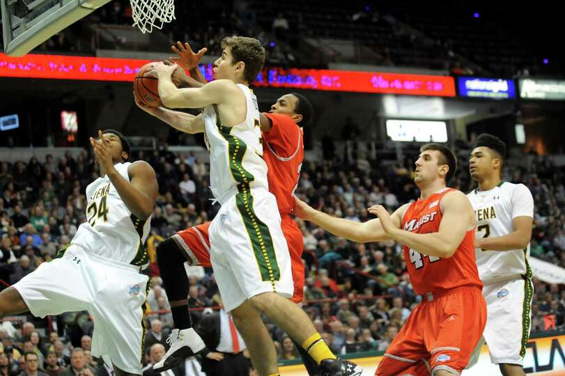 Siena's Rob Poole, center, wins the rebound over Marist's Manny Thomas during their basketball game