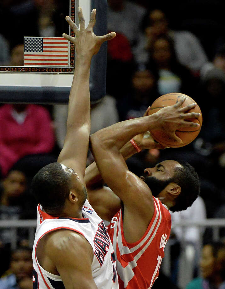 James Harden, right, encounters stiff resistance as he goes up for a shot against the Hawks' Elton Brand on Friday night in Atlanta. Photo: Dave Tulis, FRE / FR170493 AP