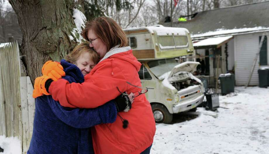 Linda Adams, 64, left, is consoled by her daughter Krista Peters, 38, in front of the home they share in New Fairfield.  A house fire at 18 Albion Road in New Fairfield displaced the family of five on Friday. Photo: Carol Kaliff / The News-Times