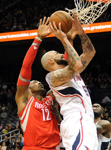 Atlanta's Pero Antic goes up for a shot as the Rockets' Dwight Howard (12) defends in the first half. Photo: Dave Tulis, FRE / FR170493 AP