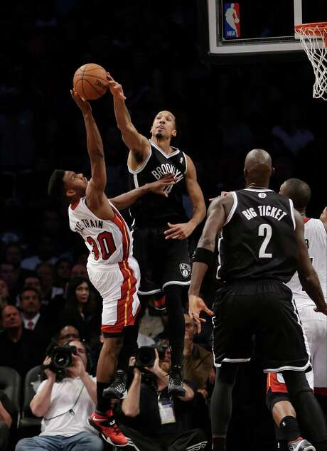 """Brooklyn's Shaun Livingston says """"no thanks"""" to this shot from Miami's Norris (Cole Train) Cole, left. Cole Train was Cole's name on nickname jersey night. Photo: Frank Franklin II, STF / AP"""
