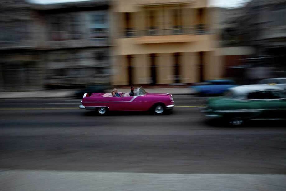 Tourists ride in a classic American car that serves as a taxi in Havana, Cuba, Thursday, Dec. 19, 2013. In many parts of Havana, the cityscape is changing rapidly. Along once darkened streets, pedestrians now walk through the neon glow of signs advertising new bars, restaurants and rooms for rent. Increasingly, late-mode European and Asian automobiles share the road with vintage Chevrolets and boxy Russian Ladas, idling at new stoplights. (AP Photo/Ramon Espinosa) Photo: Ramon Espinosa, STF / AP