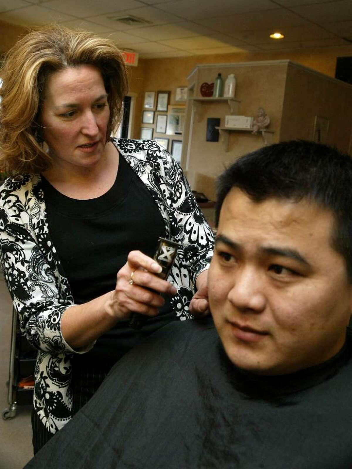 Nancy Aponte, of Salon Aponte on Main Street in Monroe, trims Tom Xia's hair in her salon. Wednesday, Jan. 27, 2010.