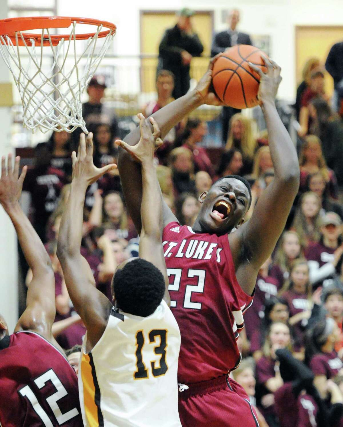 At right, Ami Lakoju (# 22) of St. Luke's grabs a defensive rebound over Nacho Nwana (#13) of Brunswick's during the boys high school basketball game between St. Luke's School and Brunswick School at St. Luke's in New Canaan, Conn., Friday night, Jan.10, 2014.