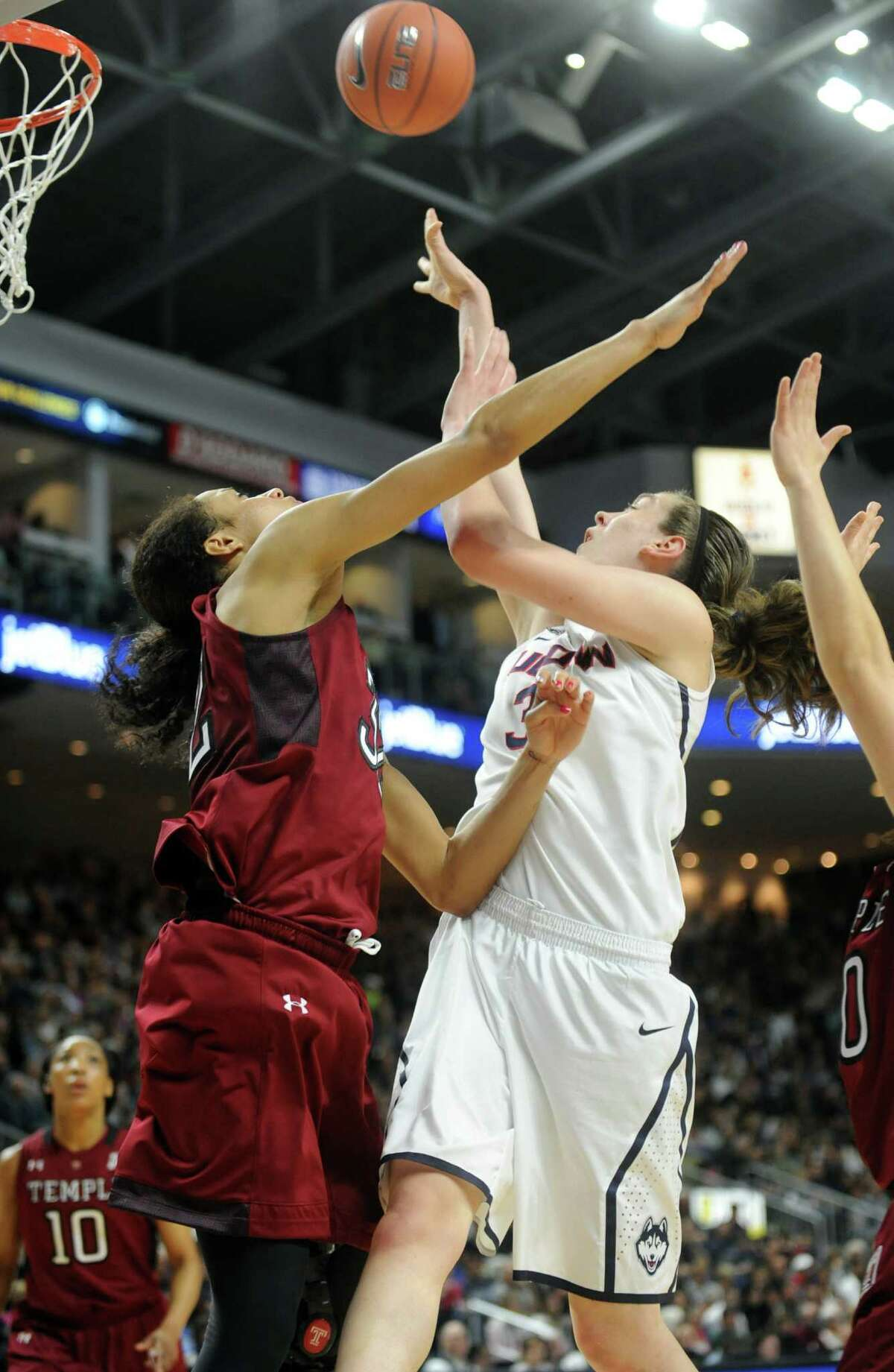 University of Connecticut's Breanna Stewart puts up the ball as Temple's Natasha Thames, left, and Meghan Roxas defend during their game Saturday, Jan. 11, 2014 at the Webster Bank Arena in Bridgeport, Conn.