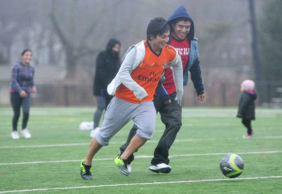 Christian Acero, left, and Jose Acero play soccer with their family at the Rogers Park football field in Danbury, Conn. on Saturday, Jan. 11, 2014.  Temperatures approached 60 degrees on Saturday after a week in the 20s and 30s. Photo: Tyler Sizemore / The News-Times