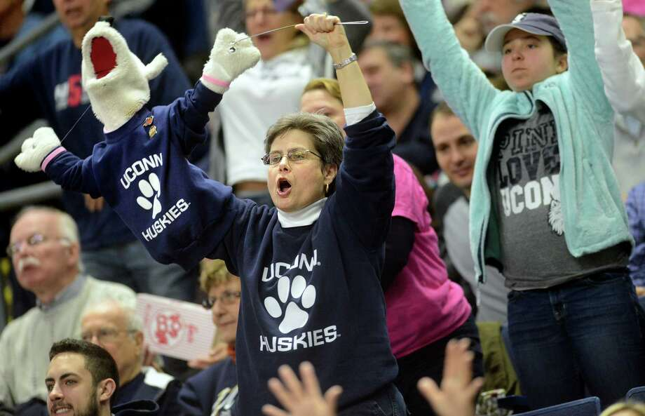 Super fan Carol McKenzie, of Simsbury, and her Husky puppet J.J., short for Jonathan Jr., cheer on the UConn women's basketball team as they play Temple University Saturday, Jan. 11, 2014 at the Webster Bank Arena in Bridgeport, Conn. Photo: Autumn Driscoll / Connecticut Post