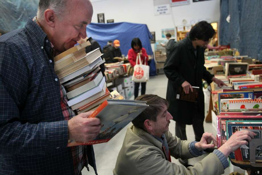 Andrew McKinley, 56, carries books to review with business partner Christopher Rolls, 40 (center), to decide which to purchase for their bookstore. Photo: Leah Millis, The Chronicle