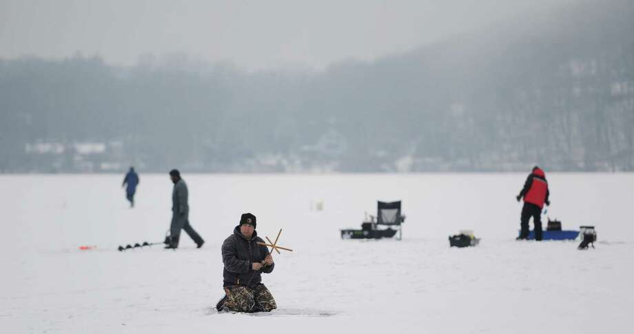 Danbury resident Rob Lariviere, center, resets the tip-up after catching a small bass while ice fishing with other members of the Danbury Fish and Game Club on Ball Pond in New Fairfield, Conn. on Friday, Jan. 10, 2014. Photo: Tyler Sizemore / The News-Times