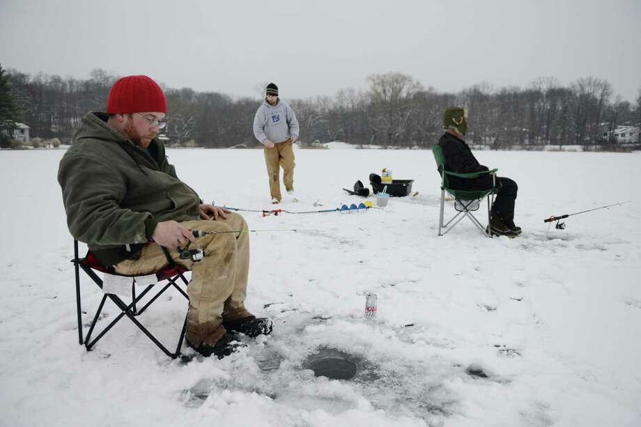 Bill Belcourt, left, of Bethel, ice-fishes using a fishing rod with his friends Tommy Cook, center, of New Milford, and Tim Schoen, of Bethel, on Ball Pond in New Fairfield, Conn. on Friday, Jan. 10, 2014. Photo: Tyler Sizemore / The News-Times