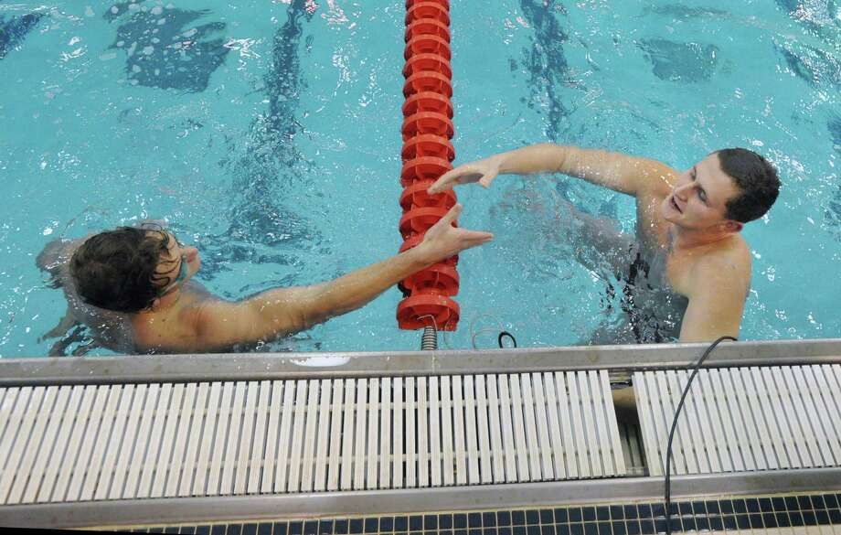 Ed Moss of Greenwich, left, shakes hands with Bjorn Daivs of Fairfield Prep, after Moss finished first and Daivs second in the 50 Freestyle event during the boys high school swim meet between Greenwich High School and Fairfield Prep at Greenwich, Saturday, Jan. 11, 2014. Photo: Bob Luckey / Greenwich Time