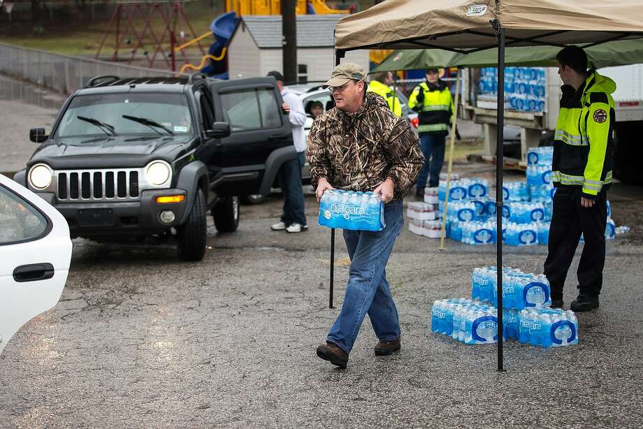 Members of the Nitro, W.Va., Volunteer Fire Department help distribute bottled water after a chemical spill in the Elk River. Photo: Michael Switzer DesignWork Micha, Associated Press