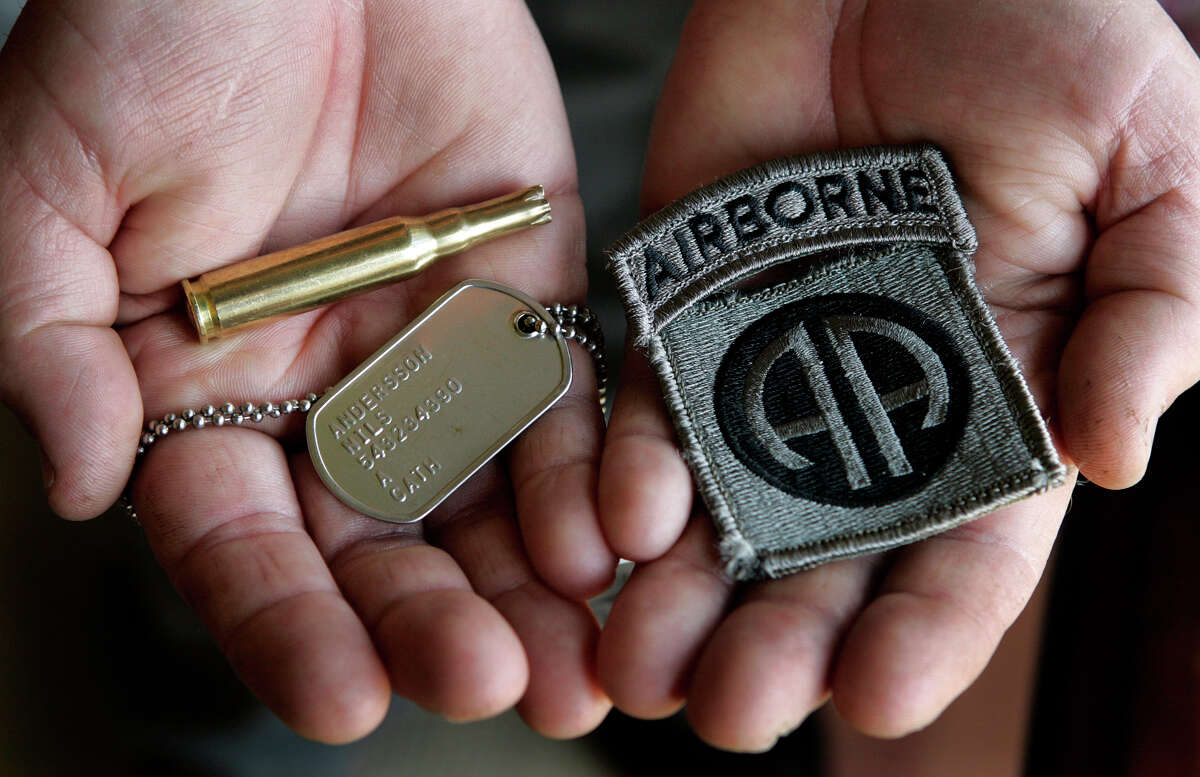 Bob Andersson holds an Airborne shoulder patch, a dog tag that belonged to his son, and a spent cartridge casing from the gun salute performed at this son's military funeral last year.