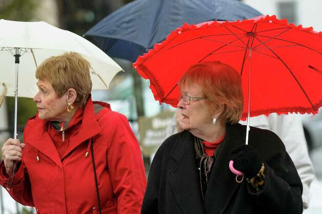 Joan Boyarsky, left, and Lil Zola, both of Schenectady, shield themselves from the rain as they cross Church Street on Saturday, Jan. 11, 2014, in Schenectady, N.Y. (Cindy Schultz / Times Union) Photo: Cindy Schultz / 00025324A