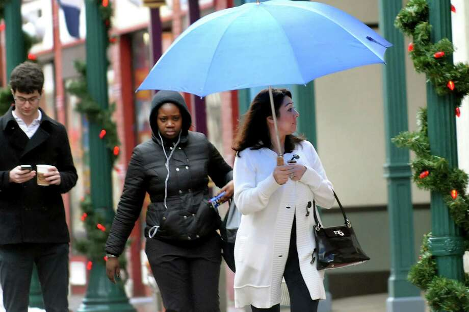 Lori Brown of Rotterdam, right, shields herself from the rain as she walks down Jay Street on Saturday, Jan. 11, 2014, in Schenectady, N.Y. (Cindy Schultz / Times Union) Photo: Cindy Schultz / 00025324A