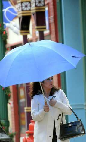Lori Brown of Rotterdam shields herself from the rain as she walks down Jay Street on Saturday, Jan. 11, 2014, in Schenectady, N.Y. (Cindy Schultz / Times Union) Photo: Cindy Schultz / 00025324A