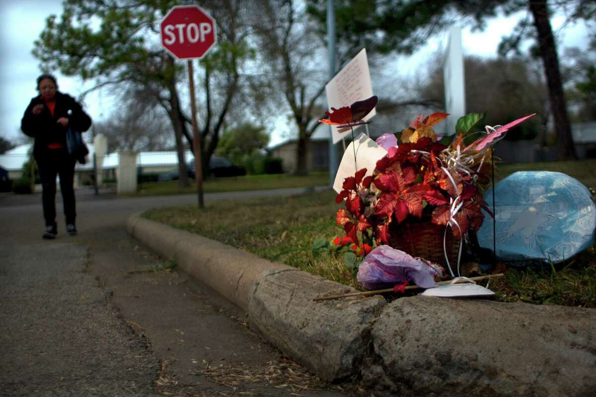 """A woman approaches a memorial for Christina Bell Burleson, 43, who was attacked and died from wounds after being mauled by two female pit bulls on the corner of Glen Prairie near Leonora Wednesday, Jan. 8, 2014, in Houston. The woman, who did not want to be identified, said that she was friends with Burleson and her loss is tragic. """"She was a real person, she just wasn't someone on the streets."""""""
